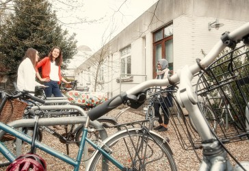 Photo of students outside near the bicycle racks